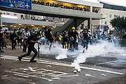 Protesters rush to pour water on tear gas canisters as they occupy roads near the Central Government Offices, during a protest against a proposed extradition law in Hong Kong, SAR China, on Wednesday, June 12, 2019. Hong Kong's legislative chief postponed the debate on legislation that would allow extraditions to China after thousands of protesters converged outside the chamber demanding the government to withdraw the bill. Photo by Suzanne Lee/PANOS