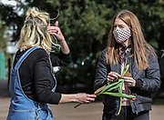13th, March, 2021. Two friends chat at an organised flower lay for Sarah Everard Cheltenham, England.