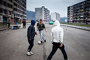 Youths play football on a road that bisects the residential blocks of Lunik IX, a decrepit housing estate almost entirely populated by Roma. Living conditions are appalling, many people do not have electricity, water or gas. Lunik IX has officially 6542 registered (12/2015) inhabitants and almost all of them are of Roma ethnicity.
