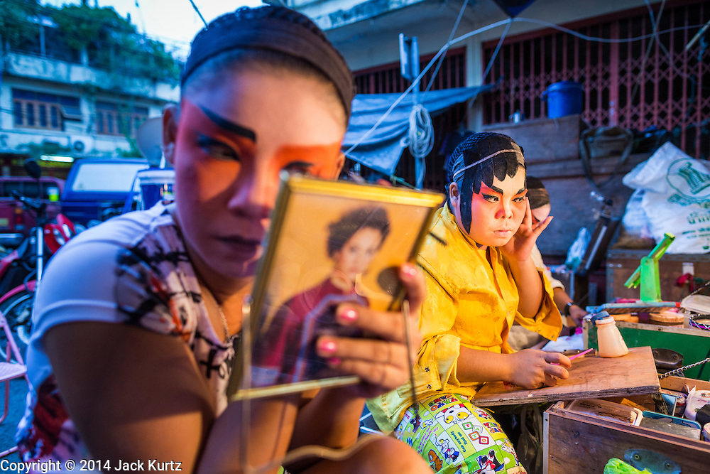 """19 AUGUST 2014 - BANGKOK, THAILAND:  Members of the Lehigh Leng Kaitoung Opera troupe put on their makeup before a performance at Chaomae Thapthim Shrine, a small Chinese shrine in a working class neighborhood of Bangkok. The performance was for Ghost Month. Chinese opera was once very popular in Thailand, where it is called """"Ngiew."""" It is usually performed in the Teochew language. Millions of Chinese emigrated to Thailand (then Siam) in the 18th and 19th centuries and brought their culture with them. Recently the popularity of ngiew has faded as people turn to performances of opera on DVD or movies. There are still as many 30 Chinese opera troupes left in Bangkok and its environs. They are especially busy during Chinese New Year and Chinese holiday when they travel from Chinese temple to Chinese temple performing on stages they put up in streets near the temple, sometimes sleeping on hammocks they sling under their stage. Most of the Chinese operas from Bangkok travel to Malaysia for Ghost Month, leaving just a few to perform in Bangkok.            PHOTO BY JACK KURTZ"""