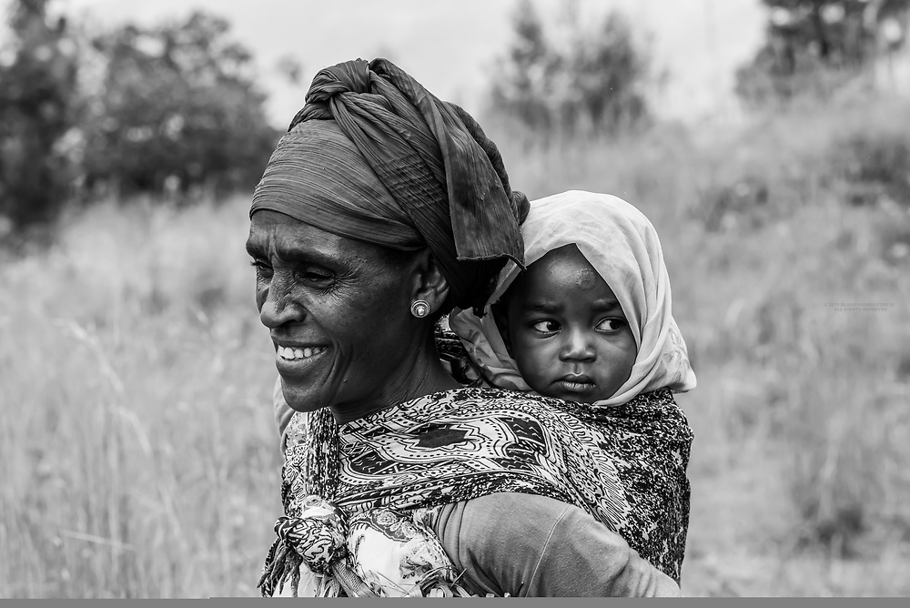 A Dorze tribe grandmother carrying a baby on her back, Southern Nations Nationalities and People's Region, Ethiopia.