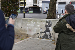 April 27, 2019 - London, UK - LONDON, UK.  People view an artwork which has appeared on a wall at Marble Arch following ten days of protests in London by Extinction Rebellion, a group demanding that governments take action to tackle climate change.  Now covered in a protective plastic cover, the artwork has been attributed to the celebrated street artist Banksy and depicts an image of a plant and a girl holding a gardening tool with the Extinction Rebellion logo on it next to the text ''From this moment despair ends and tactics begin' (Credit Image: © Stephen Chung/London News Pictures via ZUMA Wire)