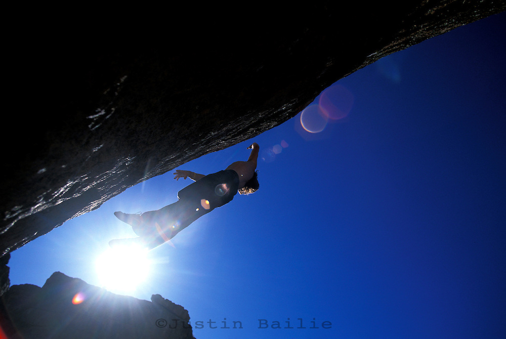 Chris Muzzillo dynoing on the Molly Boulder. Sad Boulders; Bishop, CA