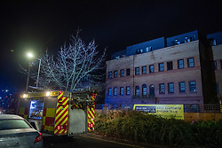© Licensed to London News Pictures. 14/11/2020. Slough, UK. A fire engine outside the building on The Grove in Slough. A high-rise flat in Slough has been gutted by fire. Royal Berkshire Fire and Rescue Servcie and partner agencies attended the fire on Saturday evening after the fire broke out, residents of an adjacent bulding were evacuated as a precaution. Photo credit: Peter Manning/LNP