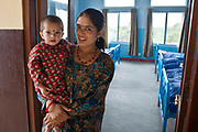A Nepalese mother holds her young child and smiles in the doorway of a ward in the Friends of Needy Children Nutritional Rehabilitation Centre, Kathmandu, Nepal.  The child is malnourished and receiving intestine nutrition treatment.