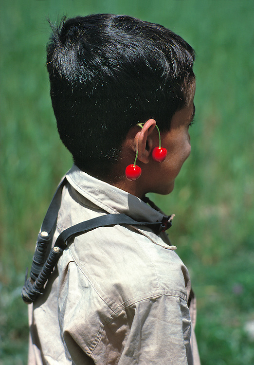 A young boy carries his slingshot around his neck and wears cherries like earrings in Gilgit, Khyber Pakhtunkhwa, Pakistan.