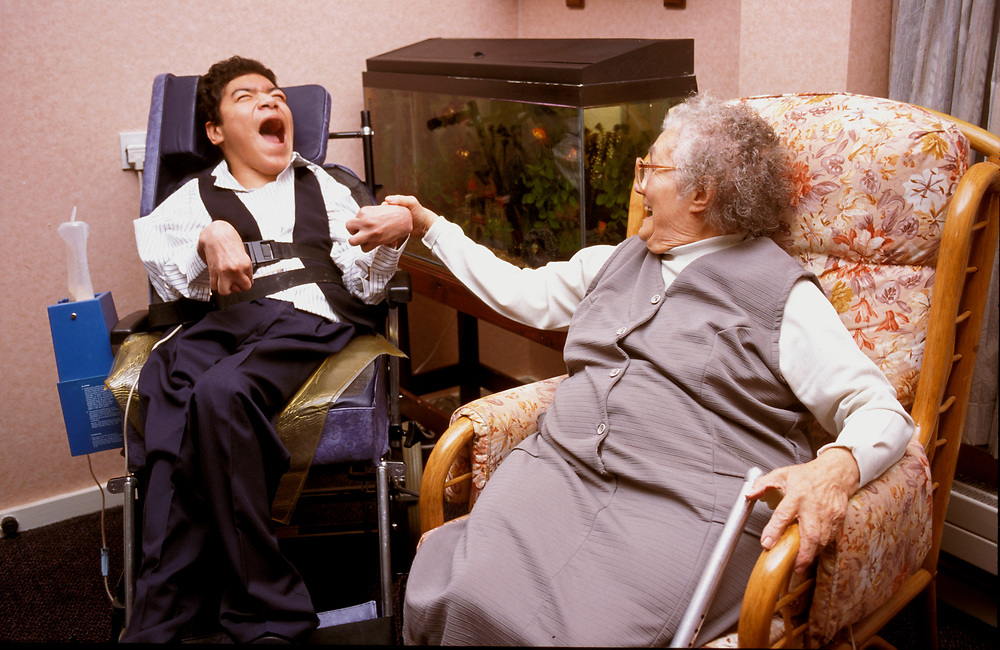 Young and old disabled friends together in residential care home,