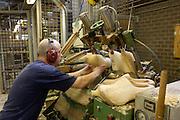 Een medewerker plaatst de klomp in een frees. Produktie bij de grootste klompenfabriek ter wereld, Klompenfabriek Nijhuis B.V. in Beltrum. Voor de productie van klompen worden speciale en zelf ontwikkelde machines gebruikt. Hoewel het principe al erg oud is, worden de productietechnieken nog steeds verbeterd.<br /> <br /> An empoyee is placing the wooden shoes in a cutter. Production at the biggest manufacturer of wooden shoes, Klompenfabriek Nijhuis B.V. at Beltrum (NL). For the production special and self developed machines are used. Although the principe of the manufacturing is very old, the techniques are still being improved.