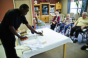 Rev. Paula Maina Waithaka prepares to celebrate mass with residents at The Abbington of Glenview healthcare residence on Wednesday, August 20th. Waithaka is Pastor at St. Catherine Laboure in Glenview. August 20th, 2014 l Brian J. Morowczynski-ViaPhotos<br /> <br /> For use in a single edition of Catholic New World Publications, Archdiocese of Chicago. Further use and/or distribution may be negotiated separately. <br /> <br /> Contact ViaPhotos at 708-602-0449 or email brian@viaphotos.com.