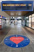 Nederland, Nijmegen, 12-5-2020 Centraal station . Vanaf 1 juni is het verplicht een mondkapje te dragen in het openbaar vervoer. In de stationshal en op het perron bij de poortjes en trappen zijn stickers aangebracht met pictogrammen om anderhalve meter afstand te houden tot elkaar . De regering en ns openen langzaam het openbare leven zodat mensen o.a. weer naar hun werk kunnen . Foto: Flip Franssen