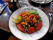 Shrimp salad with avocado, tomatoes, grapefruit and various greens served with a lemon for the shrimp at the famous Chez Janou restaurant in Paris