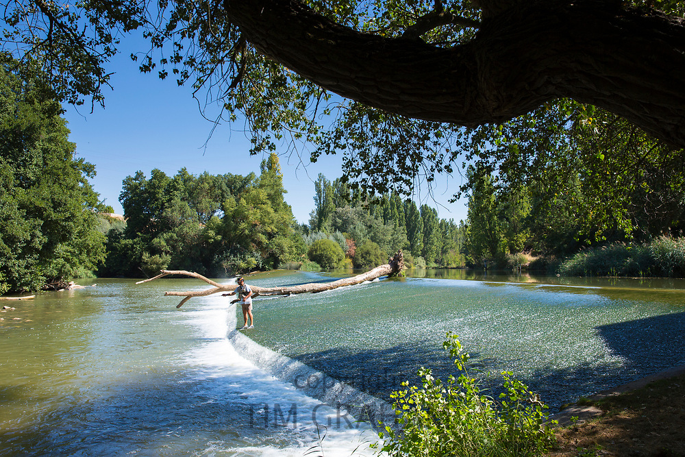 Fisherman fishing on weir on gently flowing River Duero in Castile and Leon, Spain
