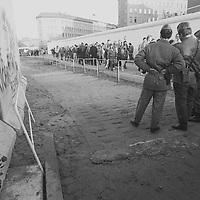 Wer es jemals geträumt hätte, daß die innerdeutsche Grenze sich ohne den Einsatz von allseits präsenten Waffen letztlich öffnen läßt wie eine Dose Ravioli, der hätte wahrscheinlich gedacht, o.k, gleich werde ich aufwachen und der schöne Spuk ist vorbei. Übergang Bernauer Straße. Mit dieser Körperhaltung gibt der DDR Soldat etwas verschämt gegenüber der Öffentlichkeit seine Machtlosigkeit zu gleichzeitig macht er sich durch das Abwinkeln der Arme etwas breiter, er pimpt sich auf.