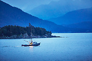 A fishing boat cruises through the dim evening light in Chilkoot Inlet, Haines, Alaska.