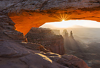 first light illuminates the underside of mesa arch in Canyonlands National Park, Utah