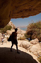 Middle East, Israel, En Gedi National Park, female hiker entering cave, with Dead Sea in distance