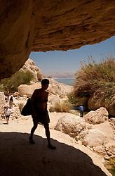 Middle East, Israel, En Gedi National Park, female hiker entering cave, with Dead Sea in distance
