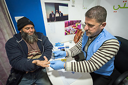 26 February 2020, Abu Dis, Palestine: 43-year-old construction worker Ziad Halabeye from Abu Dis takes a glucotest adminsitered by supervisor Ziad Paradiah, as he visits the Augusta Victoria Hospital's Mobile Diabetes Clinic. In an effort to make Diabetes services more accessible to people in the West Bank, the Augusta Victoria Hospital offers a Mobile Diabetes Clinic, which moves around to various locations in the West Bank, offering screening and routine testing for Diabietes and the symptoms it causes.