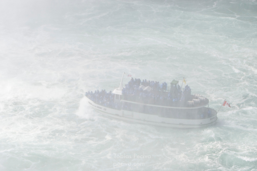 Maid of the Mist boat laboring against the current at the base of Niagara Falls.