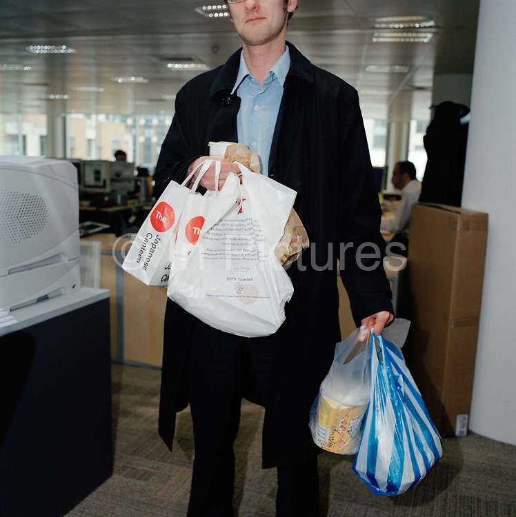 Office worker does the lunch run, at a firm of traders in the City of London, interior. From the series Desk Job, a project which explores globalisation through office life around the World.