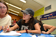 """Volunteers from Keep Tucson Together and attorney Margo Cowan provide legal assistance to persons effected by changes to DACA, or Deferred Action Childhood Arrival, which provided legal protection to those brought into the United States illegally as children, at a clinic at Pueblo Magnet High School, Tucson, Arizona, USA.  """"Edna"""", 21, entered the USA on a legal visa at the age of 9, along with her family.  Her father intended to sat in the USA to work. Her family chose to overstay their visas to avoid prolonged separation from her father.  She applied for and was granted DACA status, which lapsed in August, 2017.  With changes to DACA, she faces possible deportation if stopped by law enforcement.  She is a nursing student under the protection of DACA, but may lose that right, as she lost her job when she lost her DACA status.  She is now unemployed.  She initially arrived in the USA with her parents and two siblings.  Her parents then had two US born children.  She attends the clinic to be prepared with legal advice should she be stopped by law enforcement and be slated for deportation to Mexico. Volunteer, Sally Rusk, left, provides asistance."""