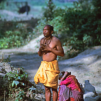Asia, Nepal, Bardia. A local Tharu man praying before bathing in river.