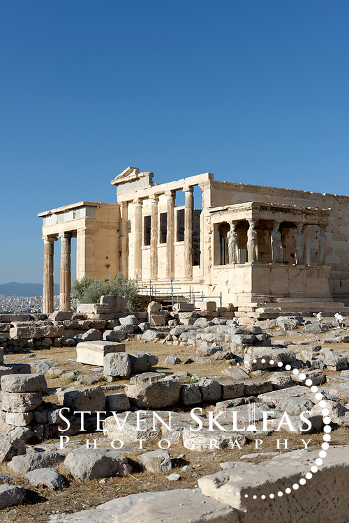 The south and west ends of the Erechtheion on the Acropolis summit. Athens. Greece. On the south side of the building is the famous Caryatid porch which has six sculptured graceful figures of maidens supporting the entablature. These figures are copies, five of the original six maidens are displayed in the new Acropolis museum and the sixth looted by Lord Elgin is on display in the British Museum. On the west end is six Ionic columns built into a low wall, the east side has a porch, with six Ionic columns and the north side has monumental Propylon also with six Ionic columns. Built between 420 and 406 BC, the elegant and unusually shaped Temple was designed to incorporate a number of ancient sanctuaries and cults including that of Athena and her olive tree and Poseidon-Erechtheus. The Acropolis of Athens and its monuments are a UNESCO World Heritage Site.