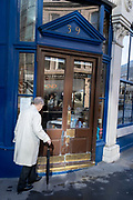 An elderly gentelman carrying an umbrella walks past the doorway of 'Sweetings', a famous fish and seafood restaurant in the City of London, the capital's financial district, aka the Square Mile, on 20th Ocotober 2021, in London, England.
