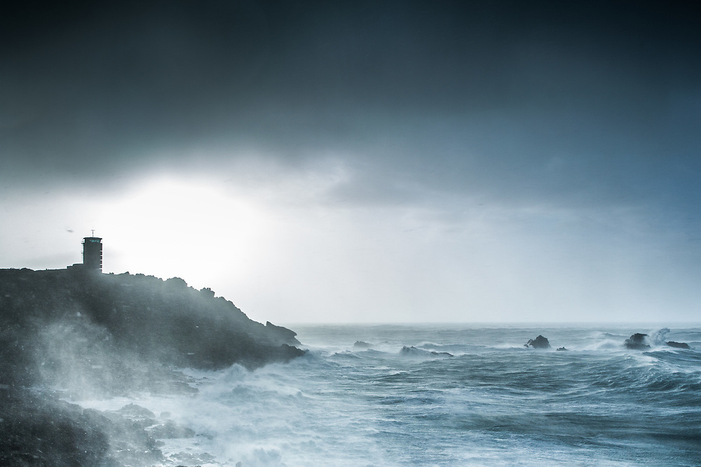 Stormy sky and gale force winds creating rough seas around the headland at Corbiere in Jersey, Channel Islands