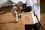 A community health nurse and a volunteer visit homes to vaccinate children against polio in the village of Gbulahabila, northern Ghana on Wednesday March 25, 2009.