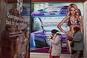 Two Muslim women walk past an image of a girl wearing a bikini in a high-street advert for sunbeds, on 26th December 2016, in Bristol's Broadmead, England UK