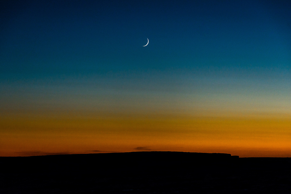 First crescent of the moon at sunset.