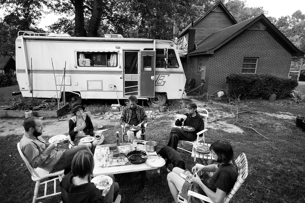 Young Farmers get together for dinner at the Circle Acres farm in Chatham County. Some farmers in the group live in the broken down RV, some sleep in nearby tents, others live in the condemned house. The group got together to eat, but also discussed strategies of water systems and usage at their different farms.