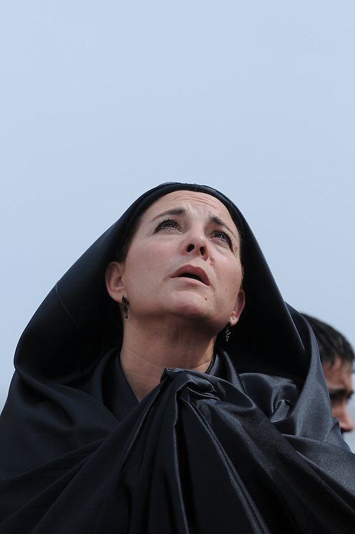 Dressed in costume after portraying Mary Magdalene during a Living Way of the Cross, or Via Crucis in Spanish, Martha De Santiago looks heavenward during an outdoor Good Friday Mass at Most Blessed Trinity Parish in Waukegan.