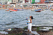 Middle aged Brazilian woman, in traditional Candomble dress of white, praying and making offerings of flowers to the sea in honour of Yemanja. February 2nd is the feast of Yemanja, a Candomble Umbanda religious celebration, where thousands of adherants visit the Rio Vermehlo Red River to pay their respects to Yemanja, the Orixa goddess of the Sea and water.