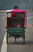 A small child sleeps in the back of a tricycle on a highway near Baodi, in Tianjin Municipality.