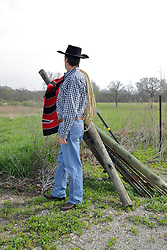 An aging man dressed in western fashions looks the part of a cowboy from days gone by in the American Old West. Accessories include a cowboy hat, boots, denim, sisal rope, western style belt and a saddle blanket on the fence in the background. Wood and Steel fence posts are stacked together with the spares leaning against strands of barbed wire that complete the fence. This image available for EDITORIAL USE ONLY. A release may be required. Additional information by contacting alook at alanlook.com