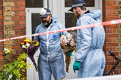Police rescue floral tributes that have been blown onto the street as strong winds hamper forensics investigators as they continue their work at the the house where the body of French film producer 34-year-old Laureline Garcia-Bertaux was found buried in a shallow grave at an address in Kew, London, after she was reported missing on Tuesday march 5th 2019. London, March 10 2019.