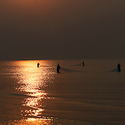 Indian women fish at daybreak with handheld nets in the waters off the coast of Puri, Orissa, India.