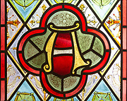 """Decorative stained glass window floral geometric pattern flowers, letter A alpha, """"I am the Alpha and Omega"""", Easton Royal, Wiltshire, England, UK"""