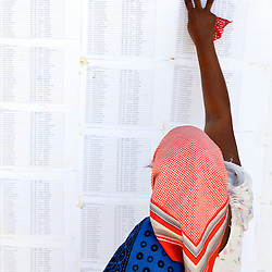 Dar Es Salaam, 30 October 2010.A Tanzanian woman checks the voter list in a polling station of Dar Es Salaam during the presidential election day..The European Union has launched an Election Observation Mission in Tanzania to monitor the general elections, responding to the Tanzanian government invitation to send observers for all aspects of the electoral process..The EU sent this observation mission led by Chief Observer David Martin, a member of the European Parliament. .PHOTO: Ezequiel Scagnetti / European Union