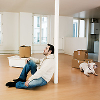 man sitting on the floor inside an empty loft appartement with bulldog