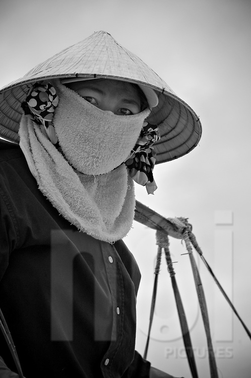 Portrait of a vietnamese woman wearing conical hat and towel over her face. Doc Let salt marsh, Vietnam, Asia