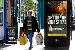 © Licensed to London News Pictures. 22/01/2021. London, UK. A woman wearing a protective face covering walks past the government's 'Don't Help The Virus Spread' publicity campaign poster in north London. The Office for National Statistics (ONS) has released figures which show the percentage of people testing positive for the virus decreased slightly in the week ending 16 January. During that period, an estimated one in 30 people had Covid-19 in London. Photo credit: Dinendra Haria/LNP