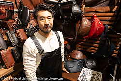 Jack Bag Leather's Daisuke Homma, who makes leather bags from old leather motorcycle jackets, in his booth at the 27th Annual Mooneyes Yokohama Hot Rod Custom Show 2018. Yokohama, Japan. Sunday, December 2, 2018. Photography ©2018 Michael Lichter.