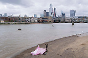 A young woman models a flowing pink dress on the Bankside foreshore of the river Thames, opposite the City of London, the capitals financial district, on 1st September 2021, in London, England.