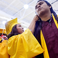 052414       Cable Hoover<br /> <br /> Kayano Cadman, left, braids Ty Yazzie's hair as they prepare for their graduation ceremony Saturday at Tohatchi High School.