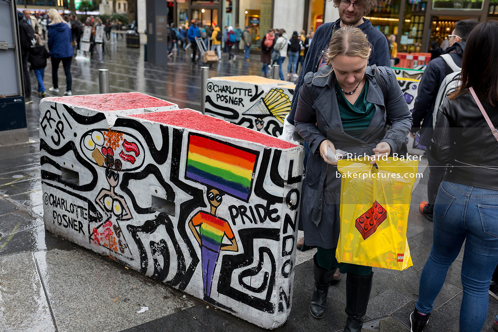 The public pass through solid decorated concrete blocks (by Charlotte Posner) and created as an anti-terrorism deterrent at Swiss Court WC2, Leicester Square, Westminster, London, England.  on 17th October 2019, in London, England.