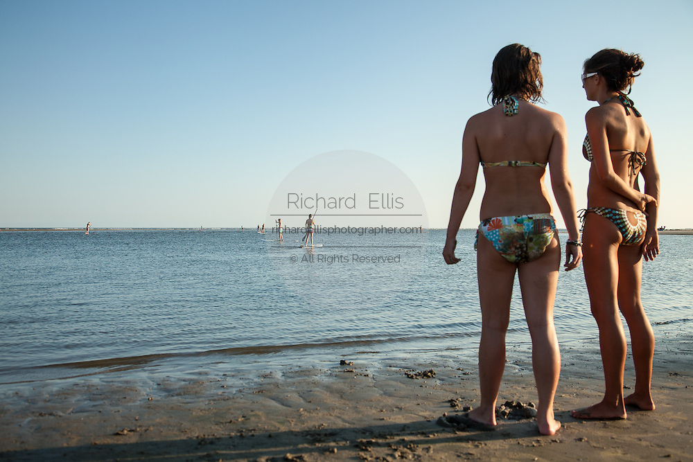 Young women watch paddle boarders on the beach on Sullivan's Island, SC.