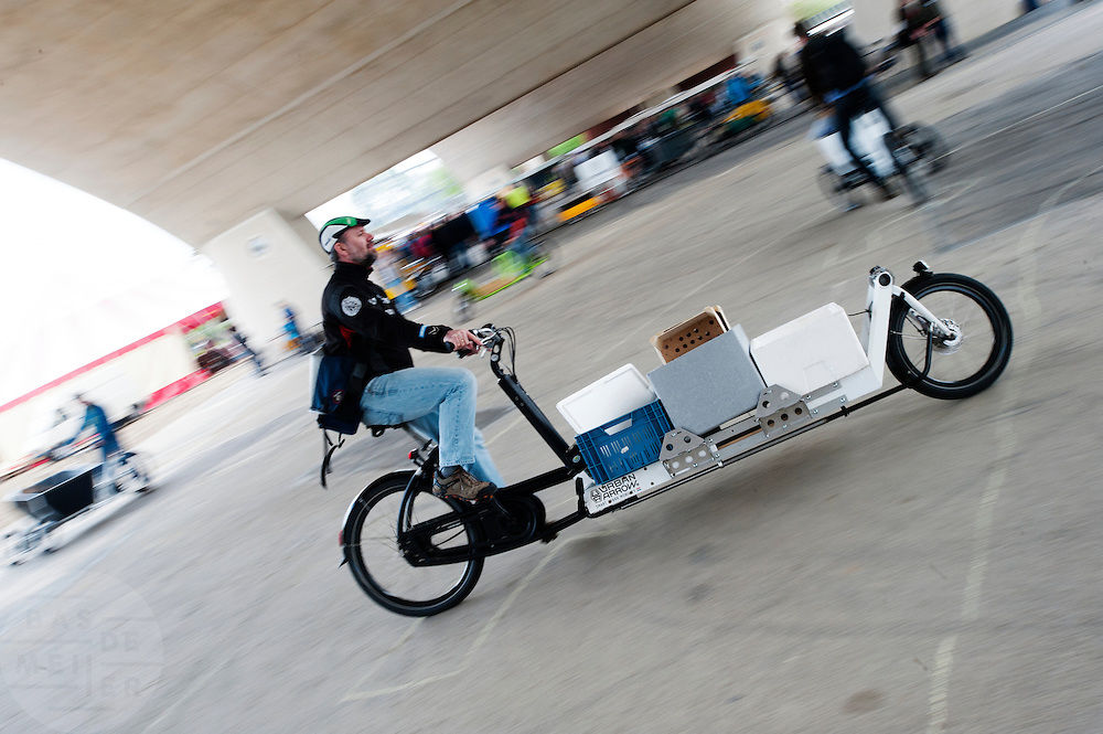 Een man probeert een transportfiets uit. In Nijmegen vindt voor de derde keer het International Cargo Bike Festival plaats. Het tweedaags evenement richt zich op het gebruik en de gebruikers van bakfietsen. Bakfietsen worden in heel Europa steeds vaker ingezet, zowel door particulieren als bedrijven. Het is een duurzame vorm van transport en biedt veel voordelen.<br /> <br /> In Nijmegen for the third time the International Cargo Bike Festival is hold. The two-day event focuses on the use and users of cargobikes. Cargo bikes are increasingly being deployed across Europe, both individuals and businesses. It is a sustainable form of transport and offers many advantages.Nederland, Nijmegen, 13-04-2014